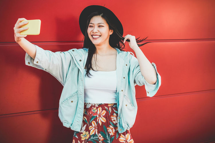 Asian social influencer woman making story for social network with smartphone camer- Happy girl having fun with new trends technology - Fashion and millennial generation activity - Focus on face Smiling One Person Holding Standing Technology Happiness Casual Clothing Selfie Camera Lifestyles Leisure Activity Young Women Portrait Real People Asian  ASIA