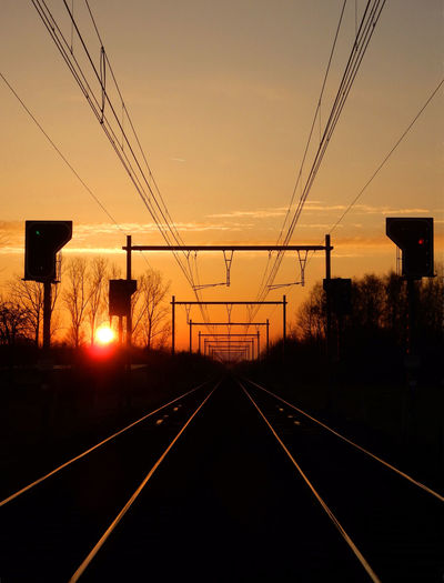 Sunset Sky Transportation Rail Transportation Track Railroad Track The Way Forward Direction Cable Diminishing Perspective Leading Lines Lines Diagonals Power Line  Technology Orange Color vanishing point Straight Orange Sun It's About The Journey
