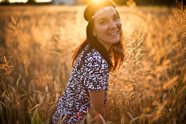 Portrait of smiling woman standing amidst plants at sunset