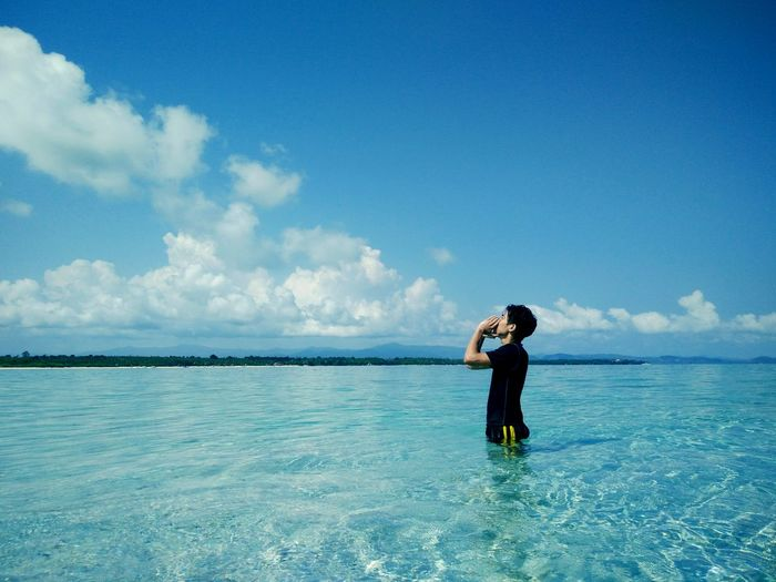 Side view of man screaming while standing in sea against blue sky