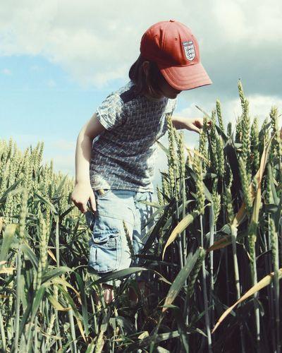 Girl in wheat field against sky