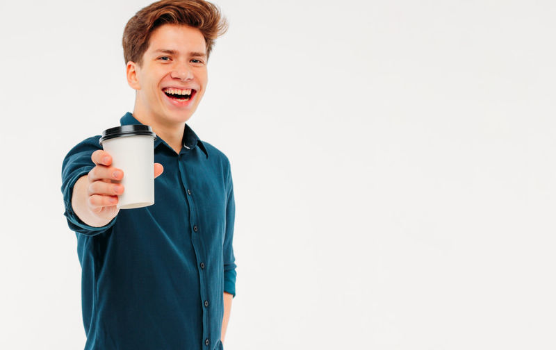 Portrait of smiling man holding coffee cup against white background