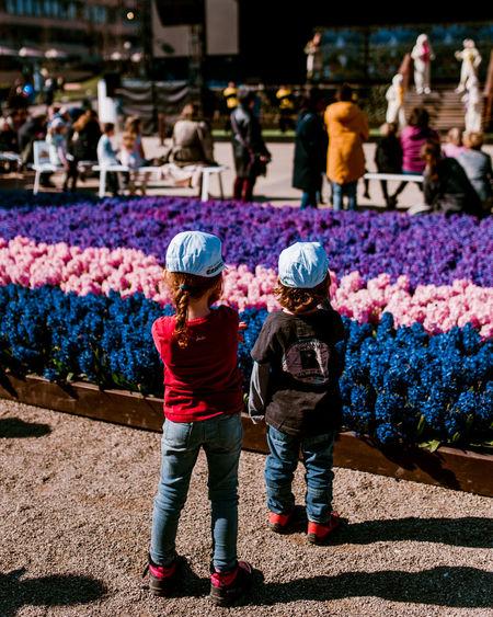 Rear View Of Siblings Standing By Flowerbed In City
