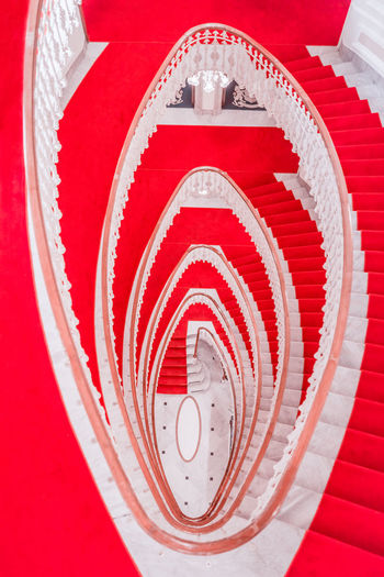 Spiral marble stairs - Spiral staircase made from marble and covered with a red carpet viewed from above Classic Architecture Spiral Staircase Spiral Stairs Spiral Stairway Architecture Photography Circle Elegant Building High Angle View Hotel Interior Indoor Photography Indoors  Marble Stairs Red Carpet Red Carpet Stairs