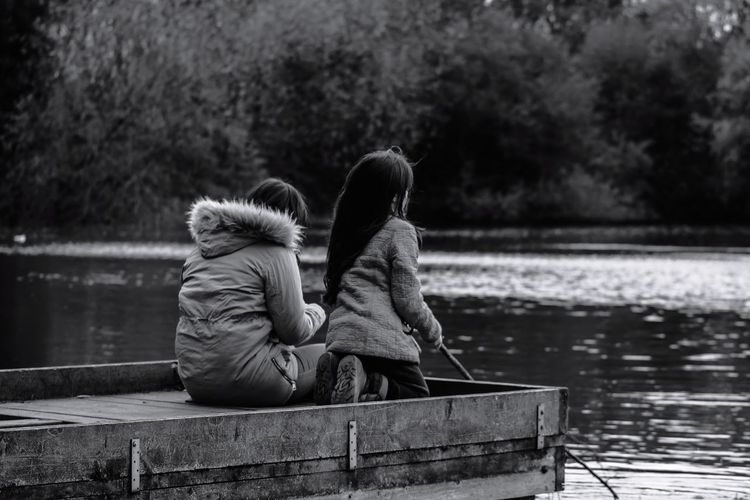 Rear view of woman with daughter sitting on pier over lake
