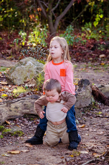 Full length of smiling girl picking up brother in forest
