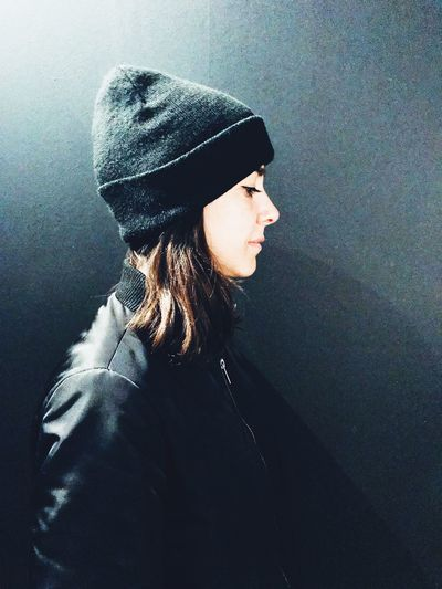 Side view of young woman wearing hat standing against wall
