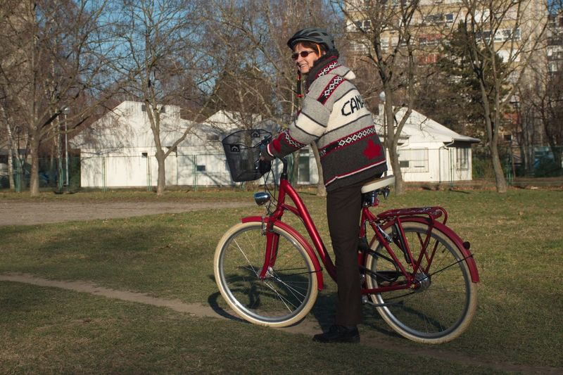 Bicycle Transportation Tree One Person Plant Full Length Sport Clothing Activity Cycling Mode Of Transportation Nature Lifestyles Motion Adult Riding Outdoors Woman Mature Adult Grass Green Helmet Red Citybike Basket House Glasses Eyeglasses  Park Wool