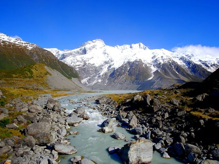 Scenic view of stream leading towards snow covered mountains against clear blue sky