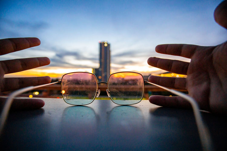 Close-up of hand holding eyeglasses against sky