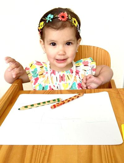 Portrait Of Girl By Table With Pencils And Paper