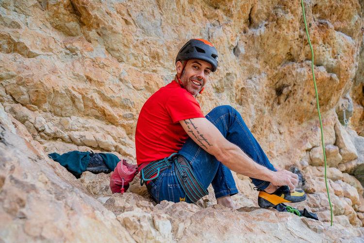 Full length portrait of smiling man holding rock
