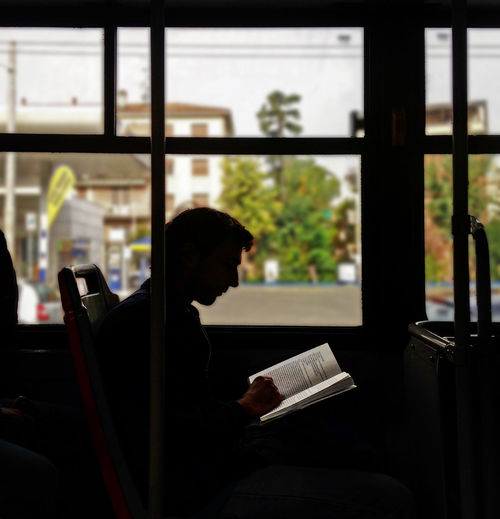 Side view of man reading book in bus