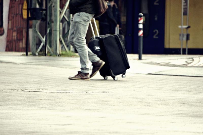 Low section of man walking with luggage in city