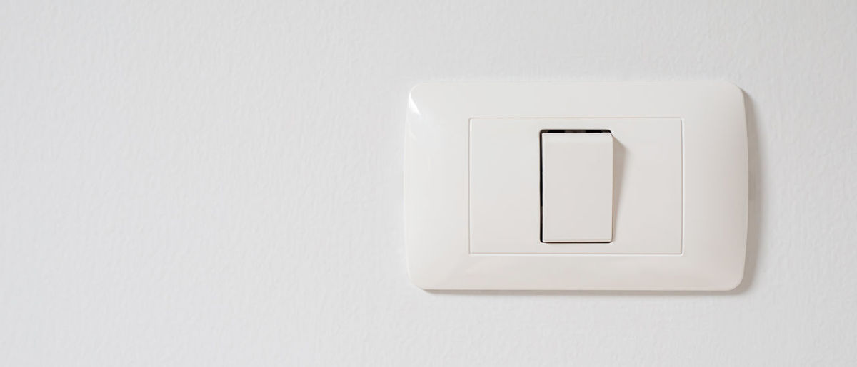 Close-up of electric lamp on wall at home