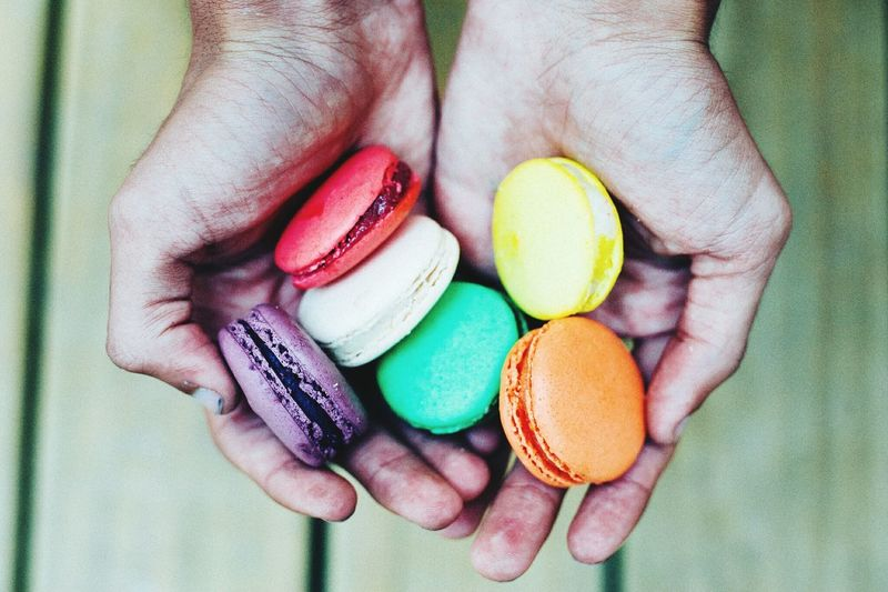 Close-up of hand holding multi colored macaroons