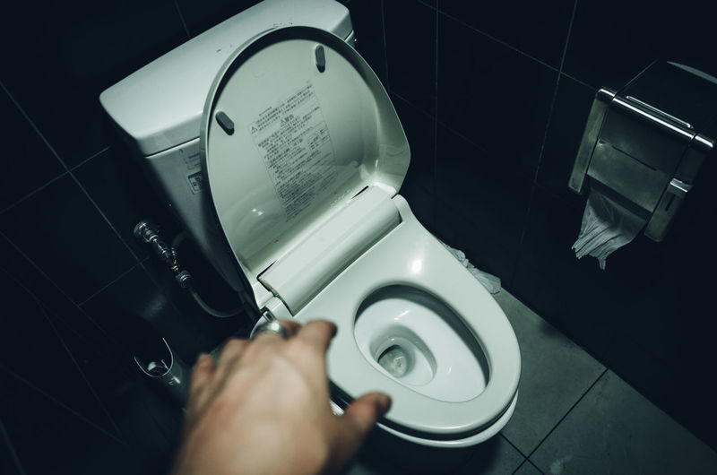 Cropped Hand Over Toilet Seat