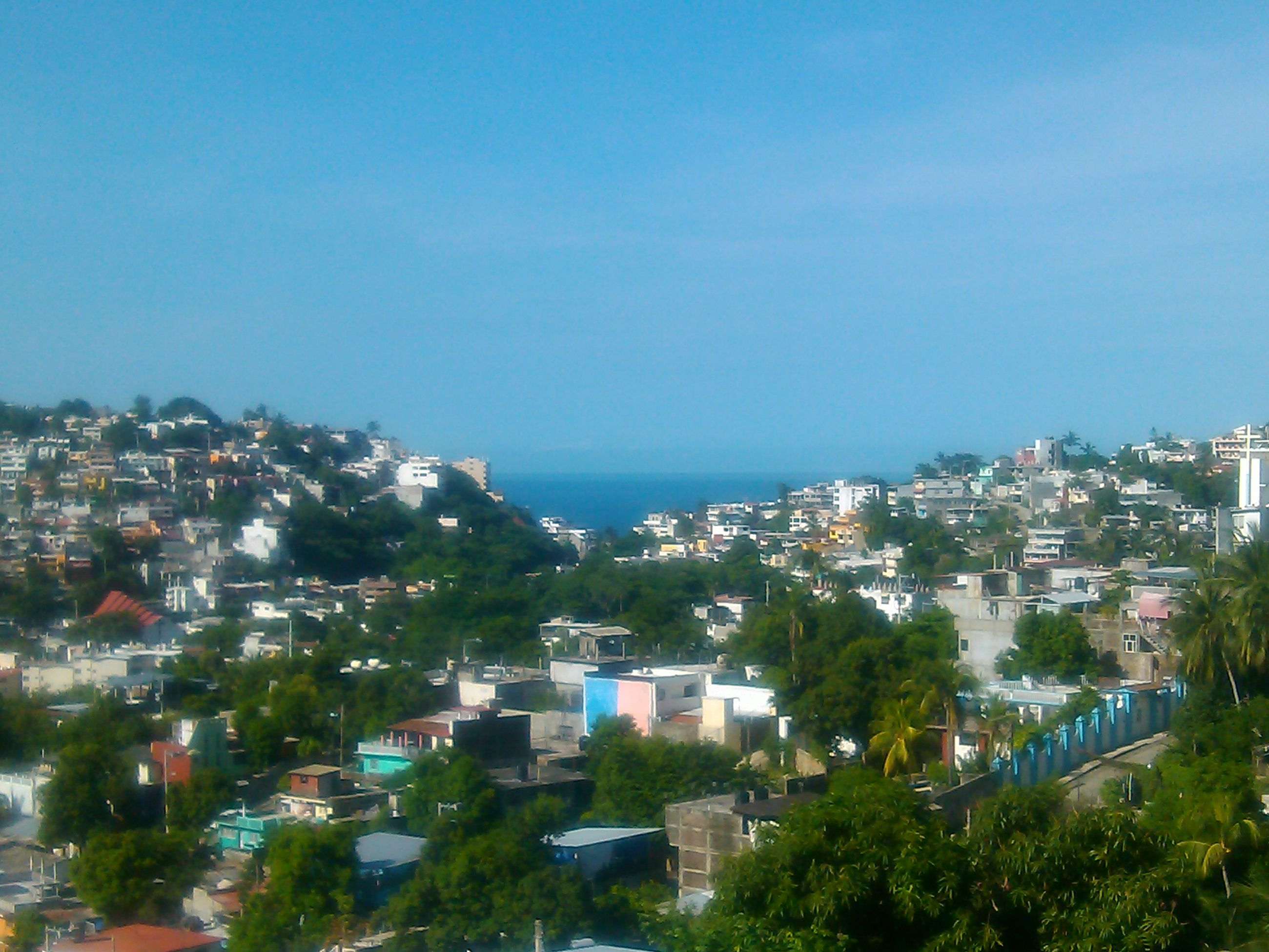 building exterior, architecture, built structure, cityscape, city, high angle view, crowded, residential district, blue, copy space, residential structure, clear sky, residential building, town, house, townscape, sea, tree, sky, horizon over water