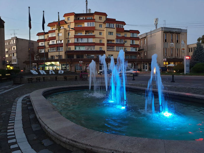 Illuminated fountain by buildings in city against sky