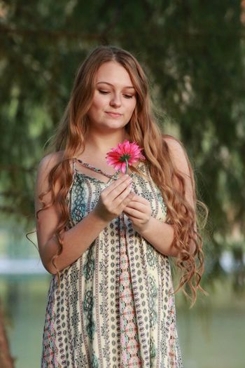 Smiling beautiful woman holding flower