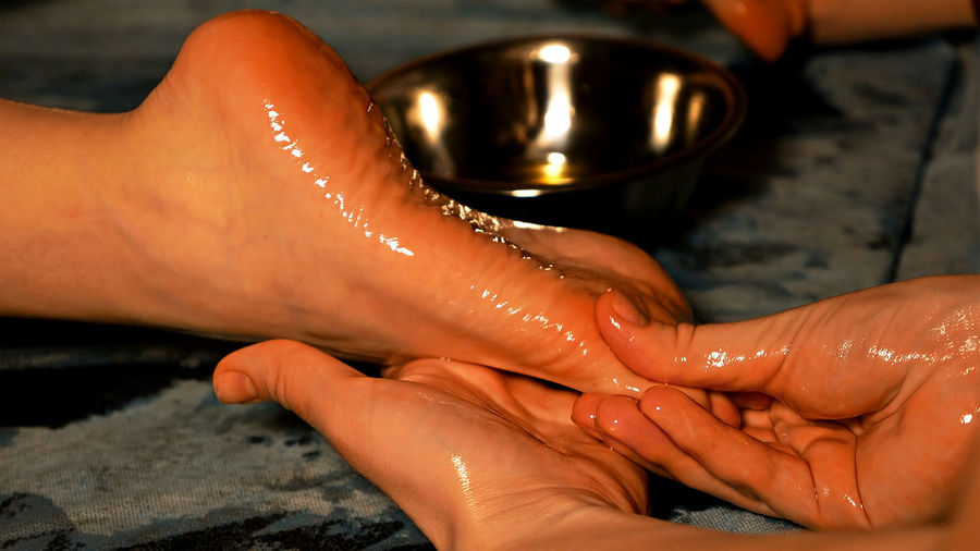 Cropped hands of male masseur massaging female customer at beauty spa