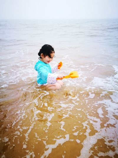 High angle view of girl playing in sea against sky