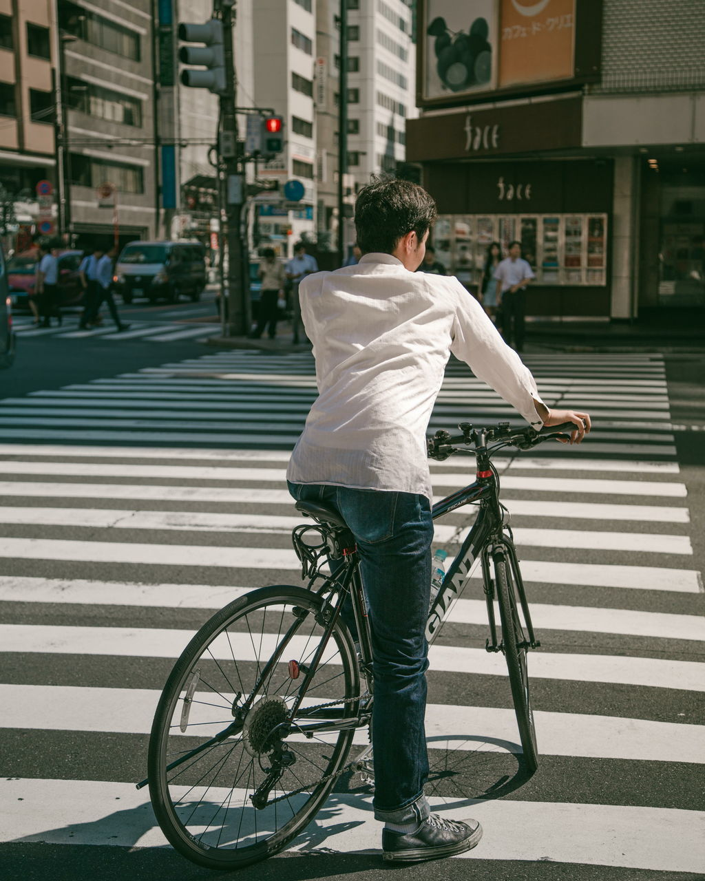 bicycle, building exterior, rear view, real people, full length, transportation, city, street, architecture, city life, one person, casual clothing, built structure, mode of transport, city street, outdoors, men, land vehicle, day, lifestyles, road, one man only, young adult, adult, people, adults only
