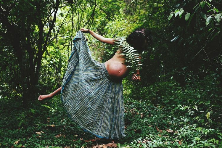 Shirtless pregnant woman holding leaves while standing in forest