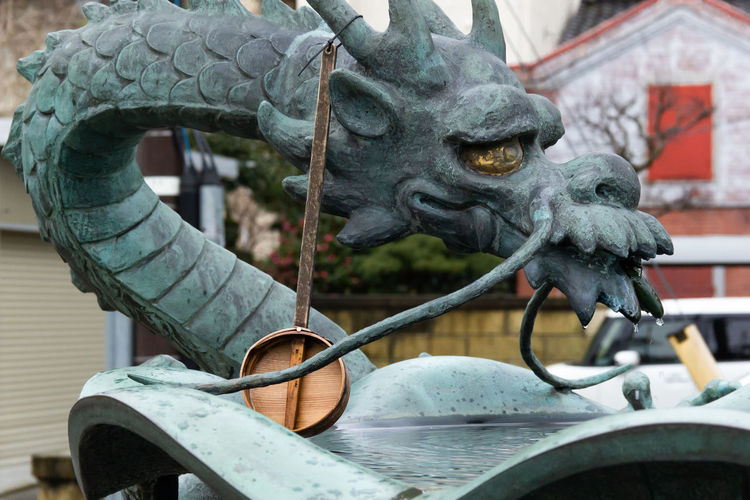 Basin with japanese dragon statue and wooden dipper for water purification
