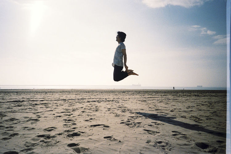 Man Levitating At Beach Against Sky