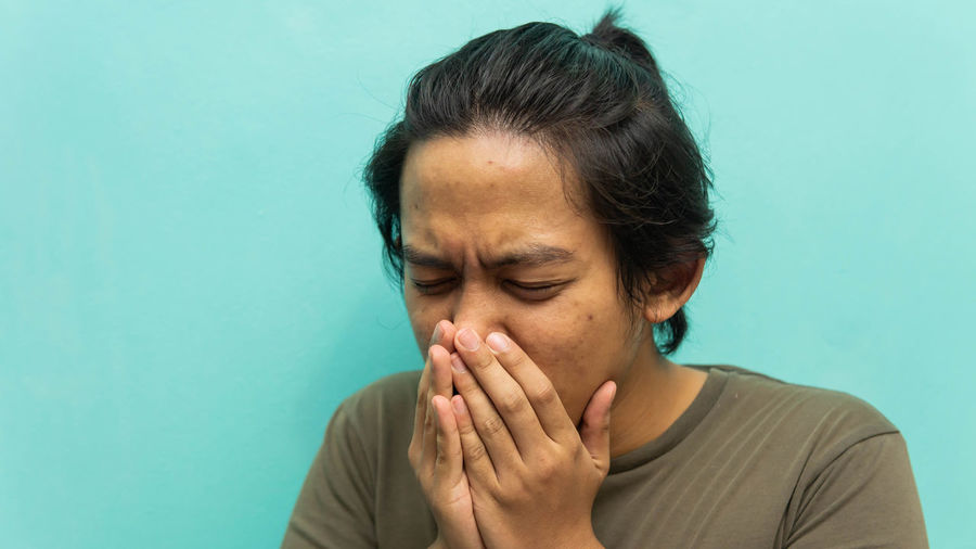 Close-up of man coughing against blue background