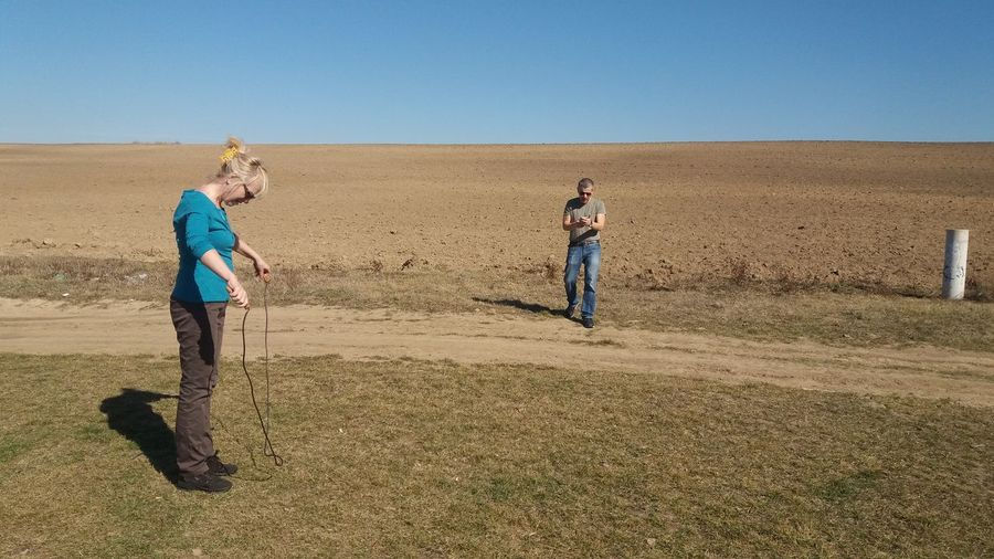 Woman looking at jumping rope while man walking on grassy field against clear sky