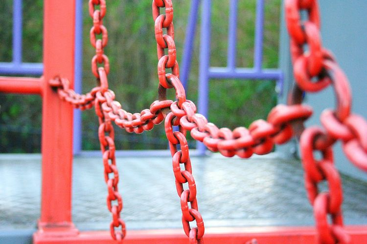 Close-up of red chain on play equipment at playground