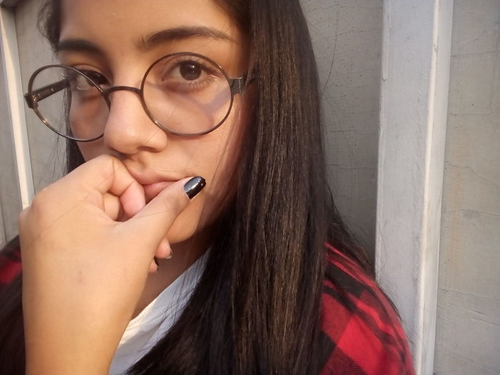 Close-up portrait of thoughtful young woman wearing eyeglasses against wall