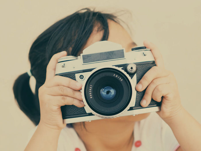 Close-up of girl photographing through camera against white background