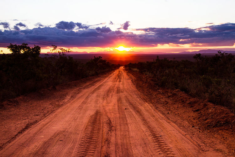 Beauty In Nature Cloud - Sky Diminishing Perspective Direction Dirt Dirt Road Environment Land Landscape Nature No People Outdoors Plant Road Scenics - Nature Sky Sun Sunset The Way Forward Tranquil Scene Tranquility Transportation Tree