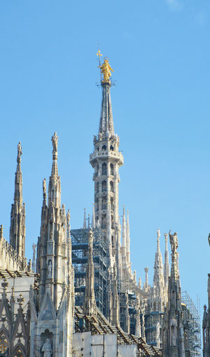 Low Angle View Of Statue At Milan Cathedral Against Blue Sky