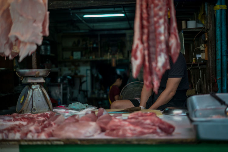 Meat seller on a stall at in local market in an old Chinese style area in Bangkok Bangkok Focus On The Story Ijas Muhammed Photography Market Thailand Beef Butcher Chef Food For Sale Journalism Market Meat Pork Red Meat Retail  Storm Cloud Street EyeEmNewHere Adventures In The City The Portraitist - 2018 EyeEm Awards The Photojournalist - 2018 EyeEm Awards