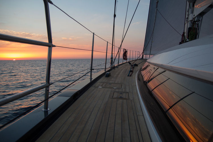 Boat deck against sky during sunset