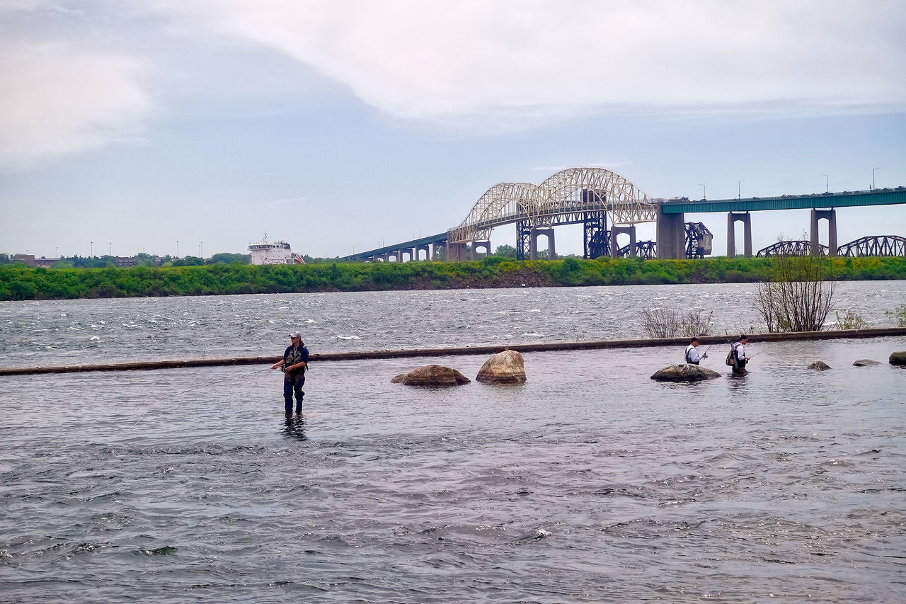 At the border between Canada and USA in Sault Ste. Marie, Canada. Bridges Ontario Sault Ste. Marie USA Architecture Border Bridge - Man Made Structure Built Structure Canada Clouds Day Fishermen Men Nature Outdoors Real People River Shore Sky Transportation Water Waterfront