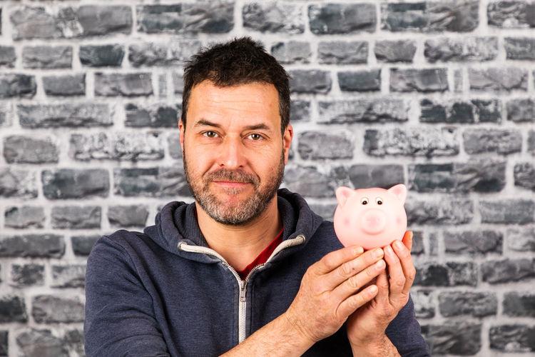 Portrait of man holding piggy bank against brick wall