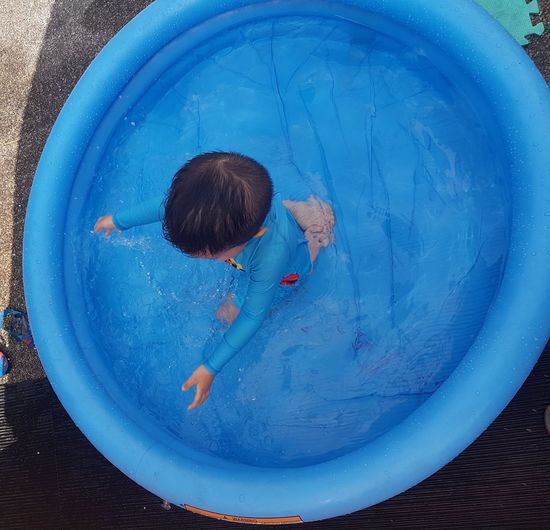 High angle view of boy playing in inflatable wading pool