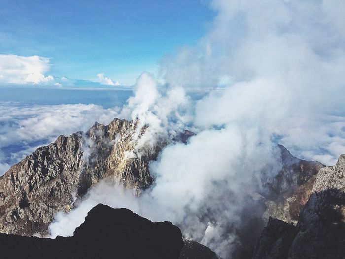 High angle view of smoke emitting from mountain against sea and cloudy sky