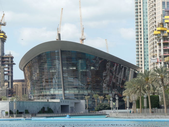 Modern Theatre, Dubai, United Arab Emirates 2019 Dubai UAE 2019 Theatre Blue Sky White Clouds Water City Palm Trees No People Waterfront Modern Architecture Modern Design Reflection In The Glass  Helicopter Cranes Entertainment Composition Outdoor Photography Sunlight Architettura Tourist Attraction  Tourist Destination Performance Art