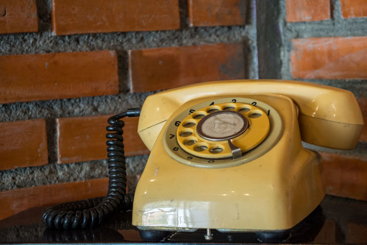 Antique Brick Wall Close-up Communication Connection Day Dial Indoors  Landline Phone No People Old Old-fashioned Pay Phone Phone Cord Retro Styled Rotary Phone Technology Telecommunications Equipment Telephone Telephone Receiver