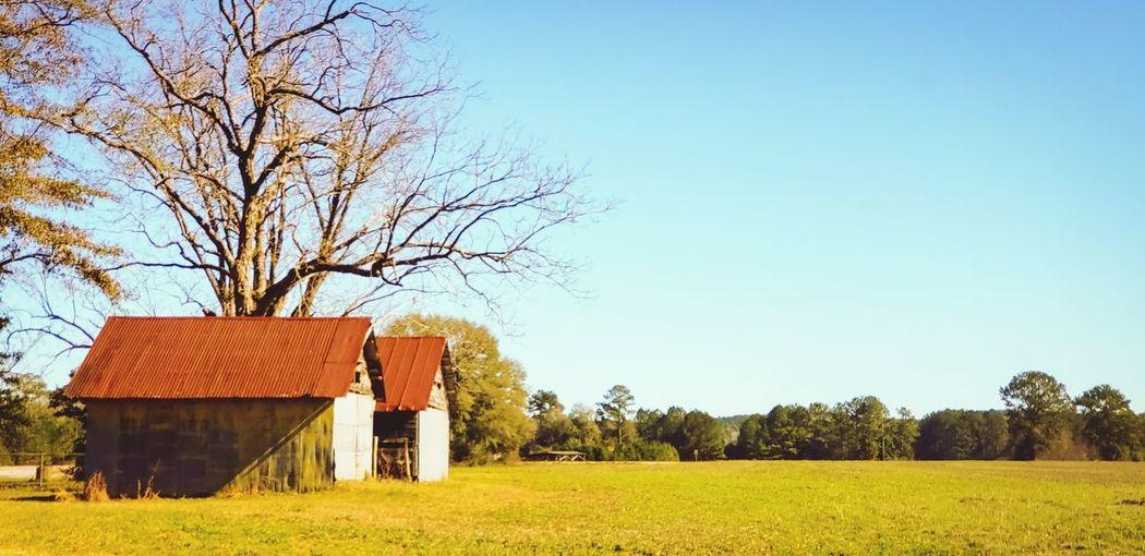 Barn on field against clear sky