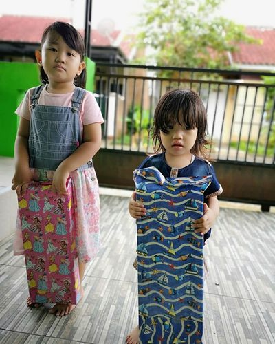 Girls Holding Patterned Fabrics While Standing On Porch