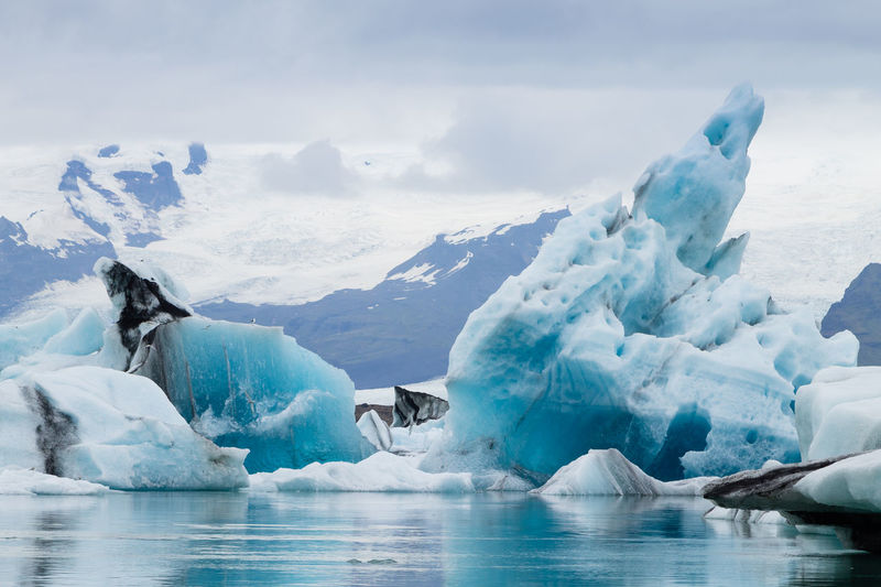 Scenic view of glacier in sea against mountains