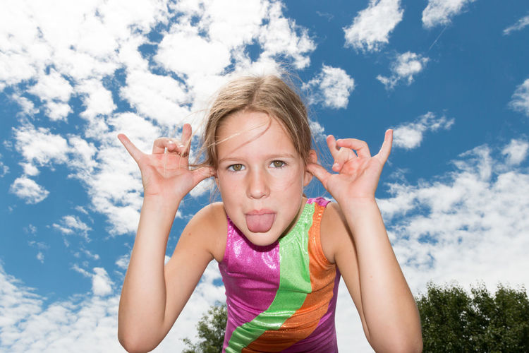 Portrait of happy girl sticking out tongue against sky