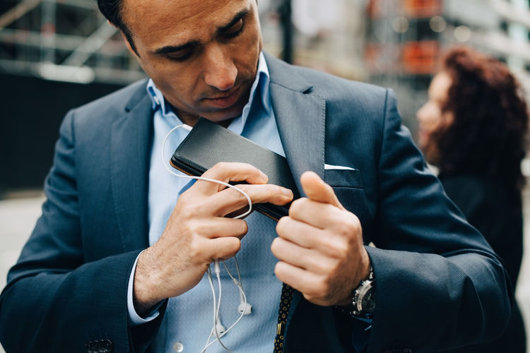 Midsection of man using smart phone